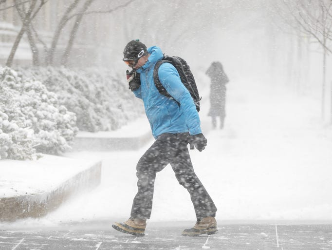 A pedestrian braces himself against high winds and