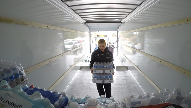 "Nick Hanshue was among those volunteering to load donated water into a rental truck to be delivered to those in need in Flint as part of a ""Fill-the-Bus with Fresh Water Drive."""