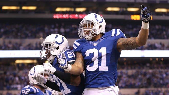 Colts cornerback Vontae Davis (21), left, celebrates his 4th quarter interception with Dewey McDonald (31), Dec. 14, 2014 at Lucas Oil Stadium. The Colts defeated the Texans 17-10 to win the AFC South.