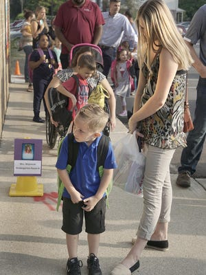 First in line for kindergarten, Keaton Stombaugh, with mom Brittany Stombaugh, takes a look down the hall of the school.