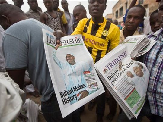 Nigerians celebrate the election outcome with the morning's newspapers at a street stall in Kano, Nigeria, on Wednesday, April 1, 2015. Amid anger over an Islamic insurgency that has claimed thousands of lives, Nigerians threw out the incumbent and elected 72-year-old former military dictator former Muhammadu Buhari in a historic transfer of power officially announced early Wednesday following the nation's most hotly contested election ever.