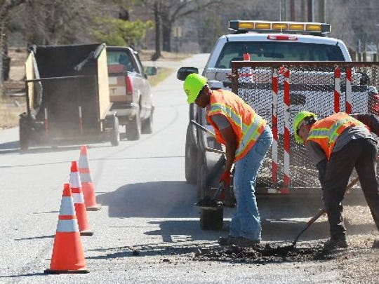 Wesley Webb, left, and Jimmy Viger of the Anderson County Roads and Bridges Division repair a pothole in February 2016.