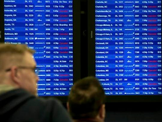 Delta passengers wait in line in hopes of catching their flight out of Hartsfield-Jackson Atlanta International Airport as monitors display flight information, Friday, Jan. 6, 2017, in Atlanta. Delta canceled about 350 flights due to inclement weather. Shoppers emptied shelves of bread and milk, road workers began working 12-hour shifts, and states of emergency were declared in Alabama, Georgia and the Carolinas ahead of a winter storm stalking the South.