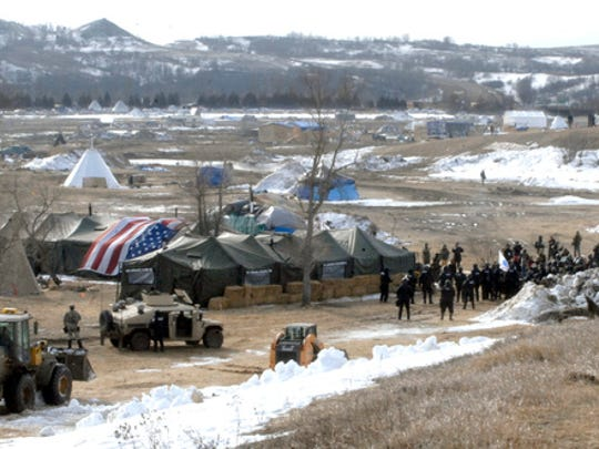 Law enforcement enters the Oceti Sakowin camp to begin arresting Dakota Access Pipeline protesters  in Morton County, Thursday, Feb. 23, 2017, near Cannon Ball, N.D. As the arrests were underway law enforcement personnel drove several large construction equipment into the camp to begin the cleanup process of razing tents and structures.