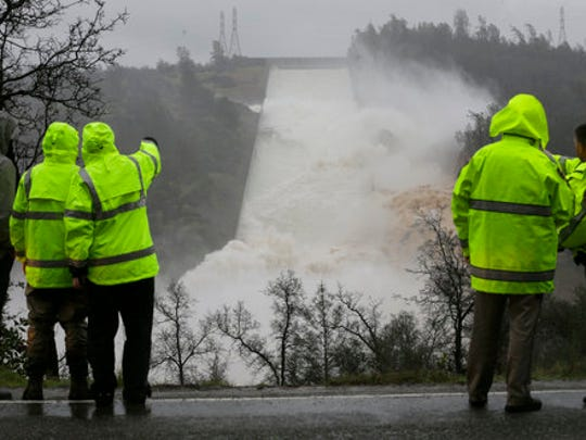 FILE - In this Feb. 9, 2017, file photo, water rushes down the damaged Oroville Dam spillway, in Oroville, Calif. Over six days, operators of the tallest dam in the United States, struggled to figure out their next move after raging floodwaters from California's wettest winter in decades gouged a hole the size of a football field in the dam's main water-release spillway.