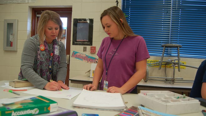 Christy Lawrence, an art teacher for Mountain Home High School, (left) helps 16-year-old Mollie  Breckenridge choose  colors for an art project Thursday at MHHS. Lawrence assigned an art project to students to bring awareness to substance abuse as a part of Red Ribbon Week.