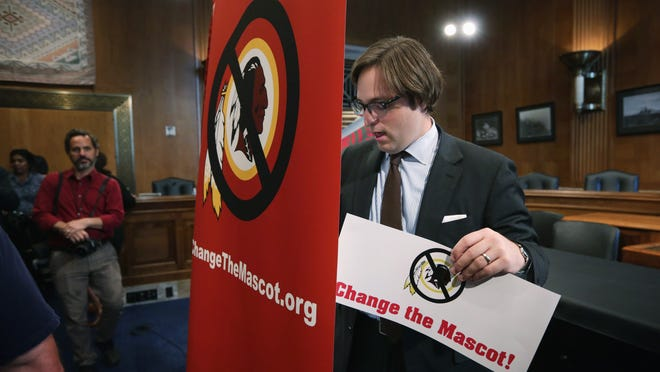 A staff brings out signs prior to a news conference Sept. 16 on Capitol Hill in Washington, DC. The group Change the Mascot held a news conference to announce new initiatives for the 2014-2015 NFL season to change the name of the Washington football team the Redskins.