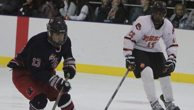 Stepinac's Justin Bernhard controls the puck while moving up the ice, with White Plains' Miles Tillman looking on, during the Guy Mathews Thanksgiving Invitational Hockey Tournament at the Ebersole Ice Rink on Saturday, November 28th, 2015. Stepinac won 7-3.