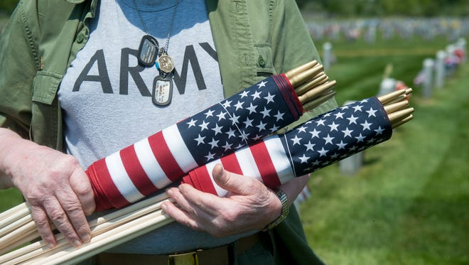 Korean War veteran Fred Connolly of Turnersville carries flags to placing by graves in the Gloucester County Veterans Memorial Cemetery in Monroe for Memorial Day weekend.