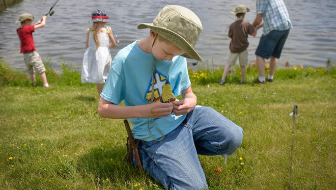 Caleb Roos, 10, Waite Park, ties a jig onto his fishing line as he and his siblings and father, Jay, fish Sunday, June 12, during a free angling contest sponsored by the St. Cloud Chapter of Muskies, Inc. at Rock Island Park Pond. The event marks the final day of Waite Park Family Fun Fest.