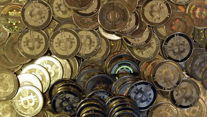 FILE - This April 3, 2013, file photo shows bitcoin tokens in Sandy, Utah. Unidentified hackers broke into the Twitter accounts of technology moguls, politicians, celebrities and major companies Wednesday, July 15, 2020, in an apparent Bitcoin scam.