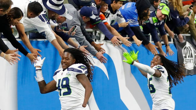 "In this Sunday, Oct. 28, 2018, file photo, Seattle Seahawks linebacker Shaquem Griffin (49) and cornerback Shaquill Griffin (26) shake hands with fans after a game against the Detroit Lions in Detroit. The NFL is partnering with three non-profit, non-partisan organizations to get out the vote as the league leverages its ""Inspire Change"" initiative. The program will support and encourage voting and civic engagement efforts of current and former NFL players, club and league personnel and fans beginning Friday, Aug. 7, 2020, until Election Day in November. The Griffins are at the forefront of the movement among players."