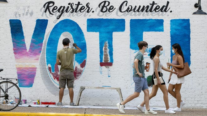 Lucas Aoki paints a mural promoting voter registration at Dobie Mall on August 24.