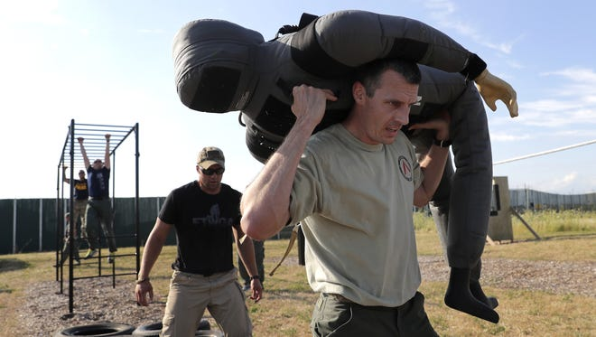 Ryan Guilette, with the Appleton Police Department, carries a dummy through an obstacle course during a competition based SWAT team training exercise at Fox Valley Technical College's Public Safety Training Center on Tuesday in Grand Chute. FVTC will host a Public Safety Day on Saturday at the training center.