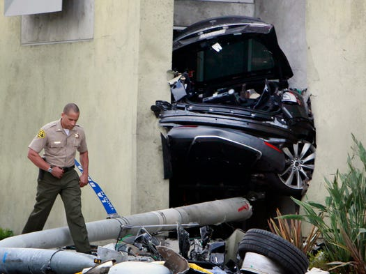 A Los Angeles County Sheriff's deputy walks past half the remains of a Tesla that wedged between two walls at Congregation Kol Ami synagogue in West Hollywood, Calif. Several were injured in the crash of the Tesla, which was reported stolen from a Los Angeles dealership. It was chased by police at speeds up to 100 miles per hour.