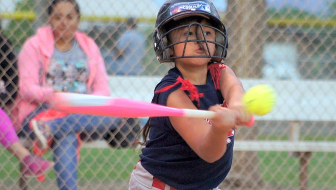 Red Sox slugger Sophia Apodaca, 8, sends the softball deep during a recent Deming Coach-Pitch girls' softball game at the Lloyd Pratz Recreational Sports Complex on Deming's east side. Apodaca and her Red Sox teammates have about two more week's of regular season left before the post-season tournament begins. The Deming T-Ball Association governs the coach-pitch teams.