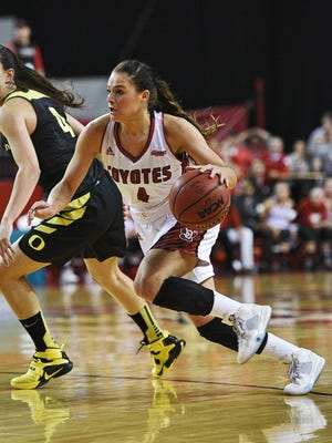 USD's Tia Hemiller (4) drives past Oregon's Maite Cazorla (also 4) during a WNIT semifinal game Wednesday in Vermillion.