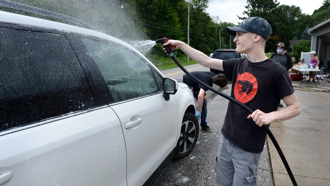 Andrew Dworek, 18, of Fairview Township, washes cars on Aug. 1 at Bonnell's Collision Center in Fairview Township. Dworek, a Fairview High School graduate, is battling a rare cancer and the car wash was to help with expenses related to his treatment.