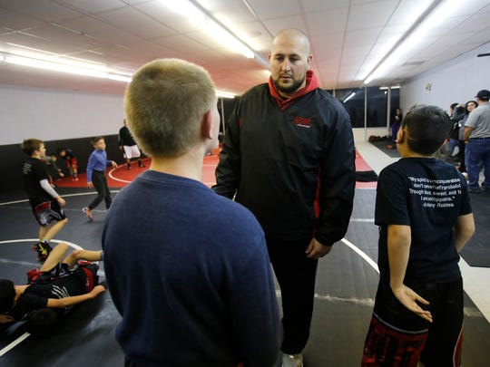 Levi Stout talks with two of his athletes Wednesday at his new wrestling academy in Farmington.