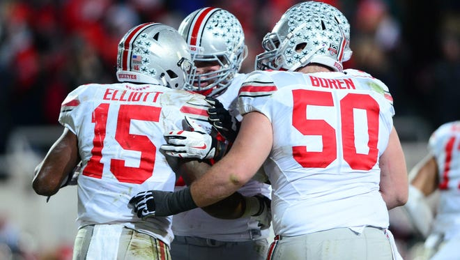 Ohio State Buckeyes running back Ezekiel Elliott (15) celebrates with teammates after scoring a touchdown during the fourth quarter against the Michigan State Spartans at Spartan Stadium.