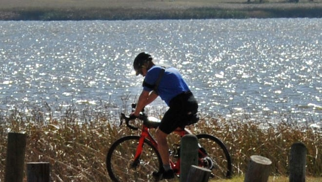 A cyclist enjoys Wednesday's warm weather while riding near Lake Wichita.