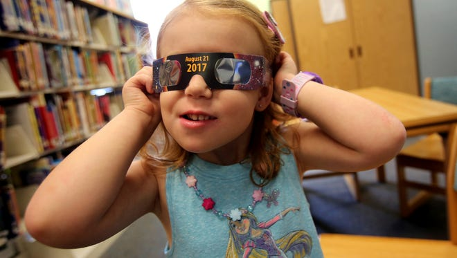 Emmalyn Johnson, 3, tries on a pair of eclipse glasses at Mauney Memorial Library in Kings Mountain, N.C. (Brittany Randolph/The Star via AP)