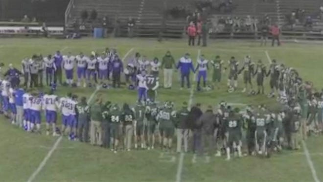 The Sand Creek and Pittsford football teams meet at midfield after official Jerry Hoffman was taken to the hospital during the game on Oct. 30.