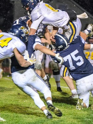 Pewamo-Westphalia quarterback Jacob Thelen (8) tries to jump over the Fowler defense Friday, Oct. 16, 2020.