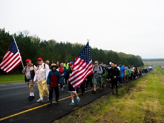 Marchers walk off the main road for a break while participating