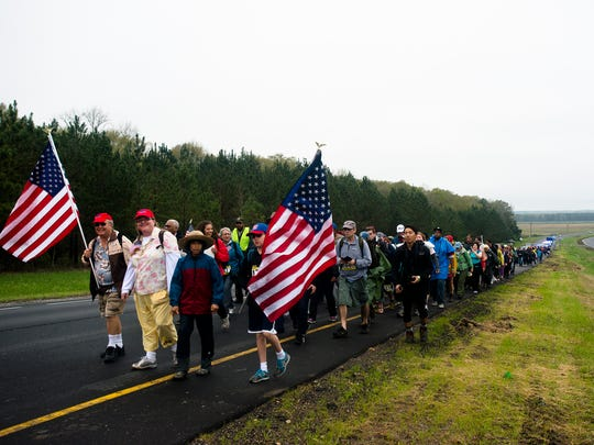 Marchers walk off the main road for a break while participating in a commemorative march of the 1965 Selma to Montgomery March as part of the National Parks Service 50th Anniversary Walking Classroom outside of Selma, Ala., on Saturday, March 21, 2015. Marchers walk 12.9 miles on Sunday stopping ending at Lowndes Interpretive Center.