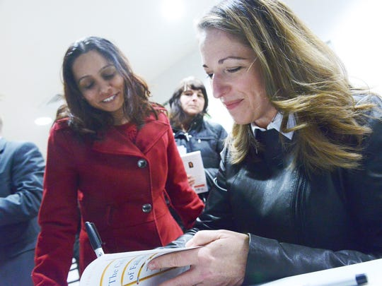 """Kalika Mondkar gets an autographed copy of Jessica Lahey's book, """"The Gift of Failure,"""" after the author's talk on Tuesday."""