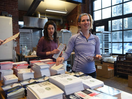 """Rachel Crampsey, owner of Montclair Bread Co. helps   stuff bags with coupons and freebies for runners participating in the """"Baker's Dozen 13.1"""" half-marathon on Saturday, March 25th. Crampsey's bakery is sponsoring the marathon."""