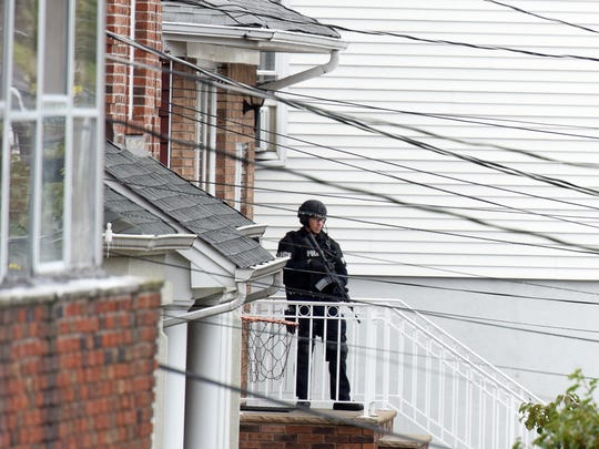 A member of the Fort Lee Police Department goes to door to door to evacuate residents of the 400 block of Summit Avenue on Sunday afternoon.