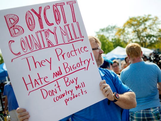 A Lansing resident holds up a sign near the Country Mill booth in protest on Sunday, Sept. 17, 2017, at the East Lansing Farmer's Market. Country Mill Farms returned to the farmer's market two days after a federal judge granted an injunction against the city and its decision to ban farm owner Steve Tennes over his decision not to hold same-sex weddings at this Charlotte farm.
