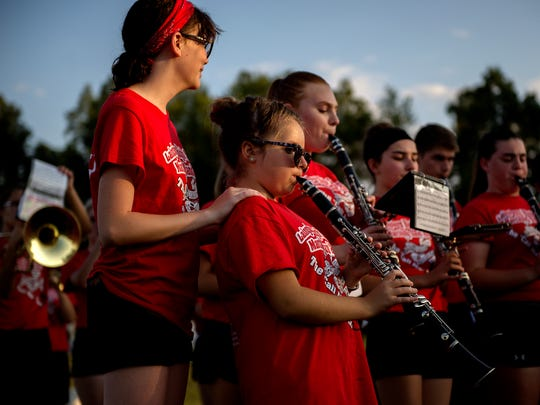 Rachael Steffens, left, rests her hands on Autumn Michels' the shoulders as the band rehearses before the start of the homecoming football game on Friday, Sept. 22, 2017, at Laingsburg High School.