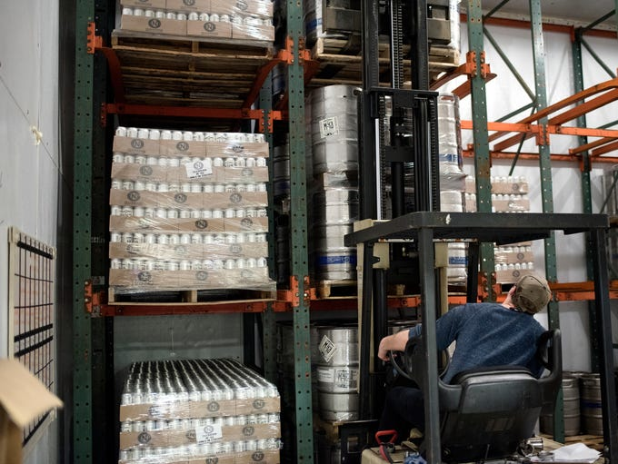 An employee moves a keg of M-43 beer into the cooler