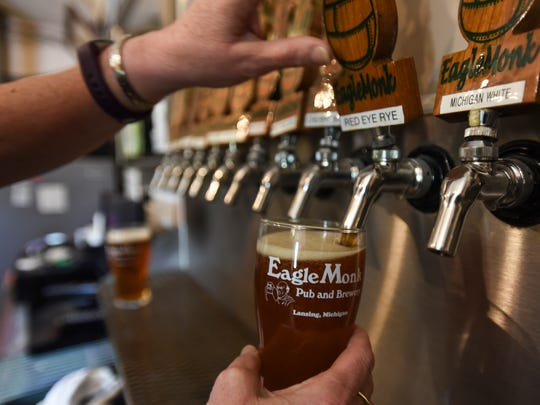 Sonia Buonodono pours a Red Eye Rye Friday, May 18, 2018.  She and husband Dan opened their EagleMonk Pub & Brewery in Delta Township in 2012.