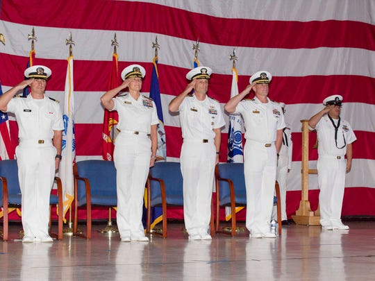 Joint Region Marianas Commander Rear Adm. Shoshana Chatfield, second from left, and the official party salute the colors at the start of the Naval Base Guam change of command ceremony at the base's Big Screen Theater on July 12, 2018. The ceremony recognized Capt. Jeffrey Grimes relieving Capt. Hans Sholley as base commanding officer.