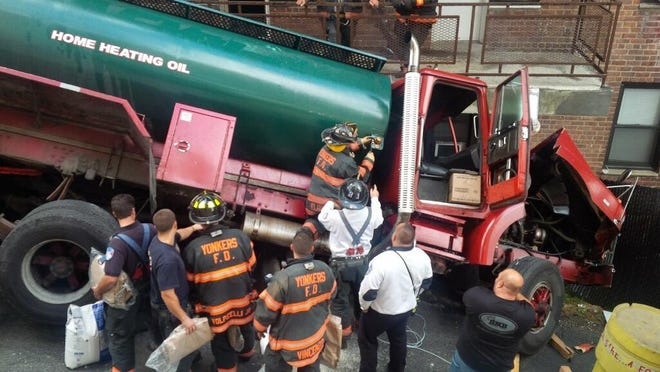 Firefighters respond to a runaway oil tanker that crashed into the side of an apartment building, tipped on its side and spilled 100 gallons of oil in Yonkers Monday.