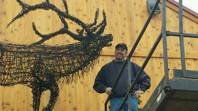 """Jeff Best stands next to the """"Bugling Elk"""" he created from barbed wire for a sporting goods store in Gaylord."""