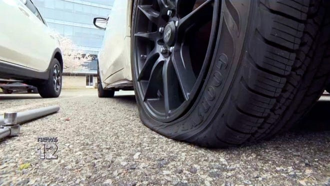 In this image from video provided by News12 Hudson Valley, one of 22 vehicles with a flat tire is seen in the parking lot outside New York-Presbyterian Hudson Valley Hospital in Cortlandt, N.Y., Saturday, April 11, 2020. Police arrested a 29-year-old man and charged him with possession of a controlled substance and criminal mischief for slashing the tires. Police said he had a small amount of PCP when he was arrested.