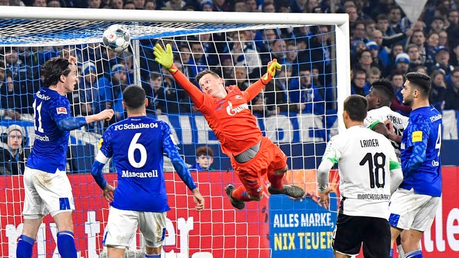 Schalke's goalkeeper Markus Schubert jumps for the ball that is saved by Schalke's Michael Gregoritsch, left, during the German Bundesliga soccer match between FC Schalke 04 and Borussia Moenchengladbach at the Arena in Gelsenkirchen, Germany, Friday, Jan. 17, 2020.