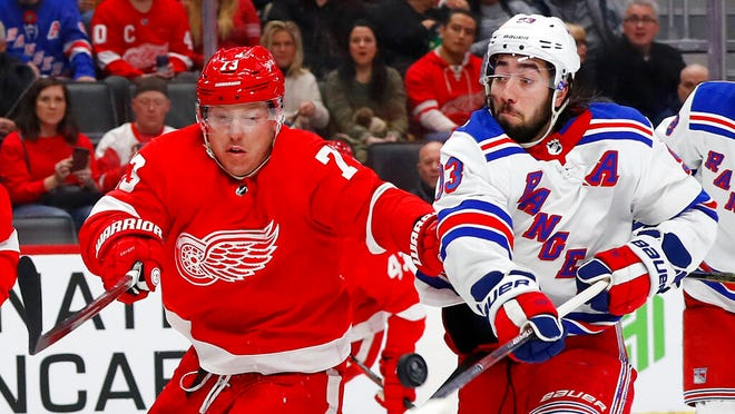 Detroit Red Wings left wing Adam Erne (73) and New York Rangers center Mika Zibanejad (93) battle for the puck in the second period of an NHL hockey game Saturday, Feb. 1, 2020, in Detroit.