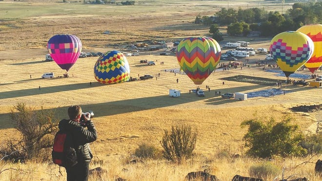A photographer captures the elegant rise of gigantic hot air balloons over the city of Montague during the 2017 balloon fair.