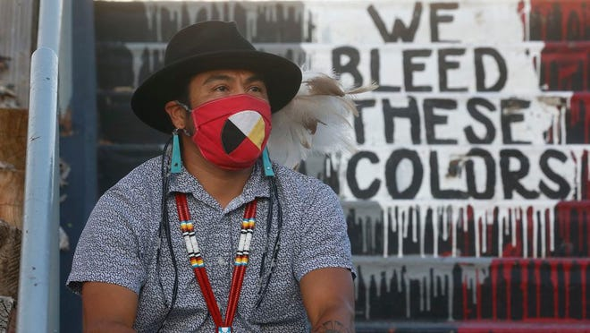 """Native American advocate Carl Moore sits near the phrase """"We Bleed These Colors"""" along a walkway which leads from the Bountiful High School parking lot up to the football field Tuesday, July 28, 2020, in Bountiful, Utah. While advocates have made strides in getting Native American symbols and names changed in sports, they say there's still work to do mainly at the high school level, where mascots like Braves, Indians, Warriors, Chiefs and Redskins persist."""