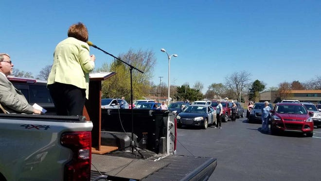 First Baptist Church Pastors Kim and Cindy Semran preach as worshippers stand outside their cars at drive-in services in the church parking lot at 1602 N. Custer Rd.