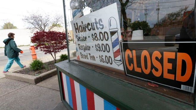 FILE - In this May 6, 2020 file photo, a woman walks past a closed barber shop in Cleveland. Small businesses are in limbo again as the coronavirus outbreak rages and the government's $659 billion relief program draws to a close. Companies still struggling with sharply reduced revenue are wondering if Congress will give them a second chance at the Paycheck Protection Program, which ends Friday, Aug. 7, after giving out 5.1 million loans worth $523 billion.