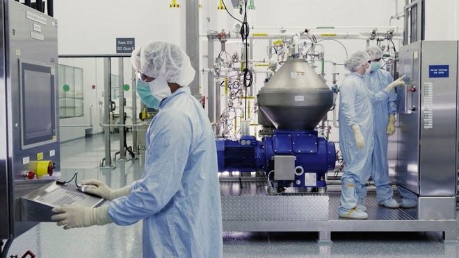 In this undated image from video provided by Regeneron Pharmaceuticals on Friday, Oct. 2, 2020, scientists work with a bioreactor at a company facility in New York state, for efforts on an experimental coronavirus antibody drug.