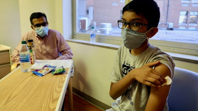 Twelve-year-old Abhinav is one of the first children to join a COVID-19 vaccine trial. He got his shot on Oct. 22 at Cincinnati Children's, the same day as his father Sharat also joined the trail. Courtesy Cincinnati Children's via USA TODAY