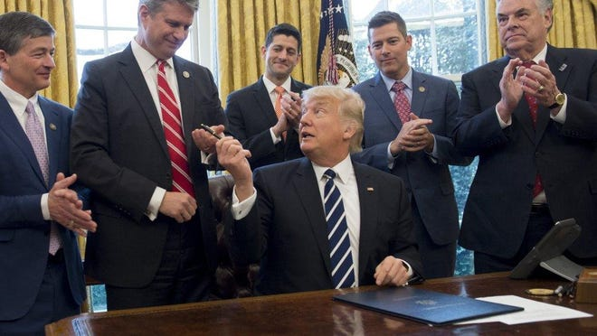 President Donald Trump hands his pen to U.S. Rep. Bill Huizenga, R-Zeeland, after signing legislation in 2017 that removed some Dodd-Frank regulations on oil and gas companies.